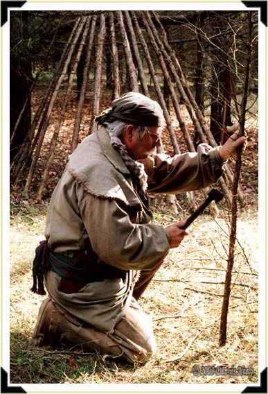 A traditional woodsman trimming branches with a belt ax.
