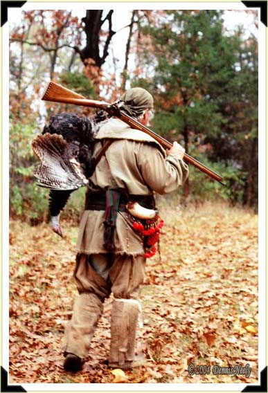 A trading post hunter walking with a wild turkey slung over his shoulder.