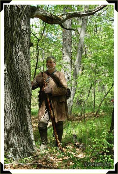 A ranger pauses behind a large oak tree