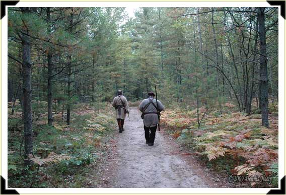 Two traditional woodsman walking a path into the wilderness.