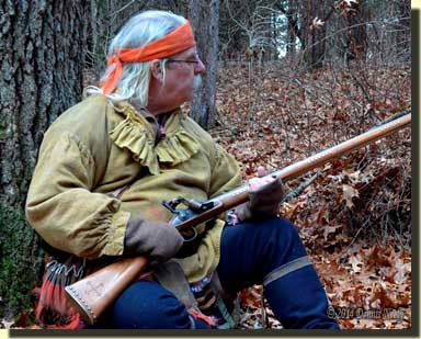 A noise causes a traditional woodsman to turn to his left.