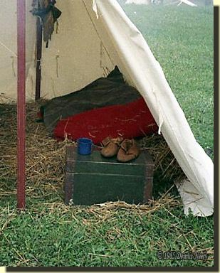 An open, 18th-century wedge tent with the straw bedding.