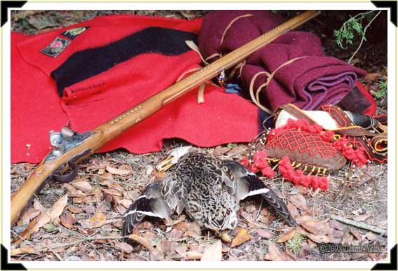 A mallard hen beside a Northwest gun and a bedroll.