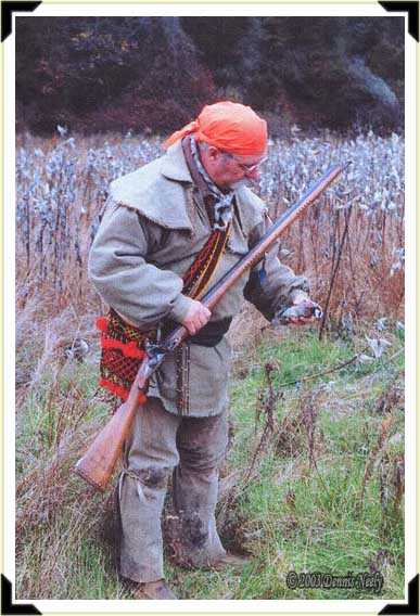 A traditional woodsman picks up a downed bobwhite quail.