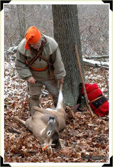 A traditional woodsman perpares to field dress an eight-point buck.