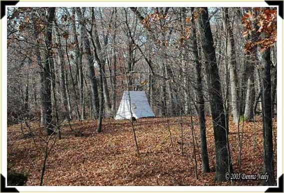 A white wedge tent stands on two ridges from the River Raisin.