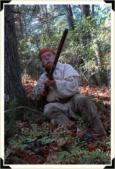 A traditional woodsman raises his Northwest gun.