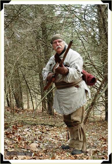 A trading post hunter raises his Northwest gun.