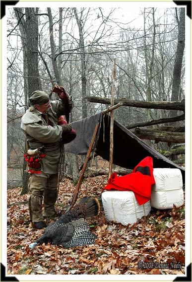 A traditional woodsman taking off his bedroll after returning to camp.