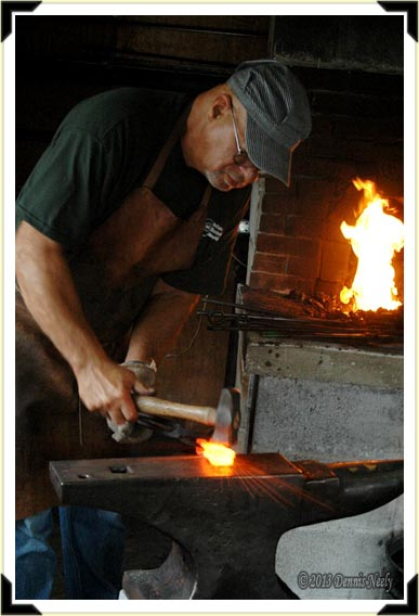 A blacksmith forges steel into an ax.