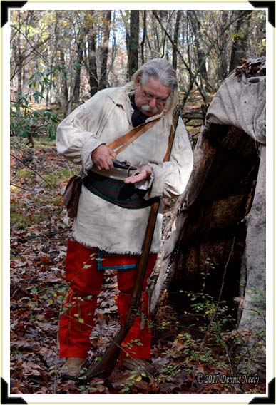 Standing outside his wigwam, a traditional woodsman measures powder with his hand.