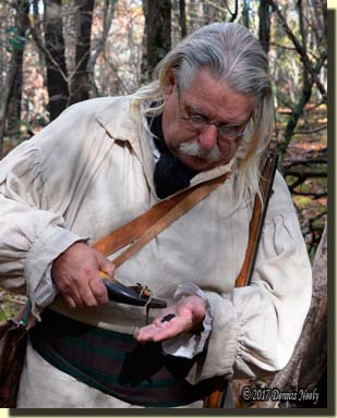 A traditional woodsman measures out gunpowder in the palm of his hand.
