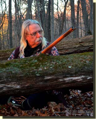 A traditional woodsman watches from behind a mossy log.