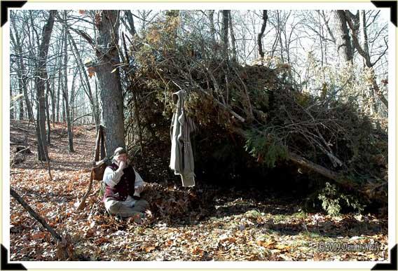 A trading post hunter sits at his brush shelter eating walnuts.