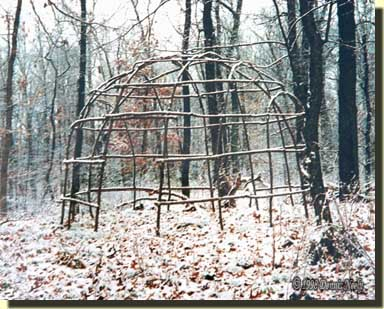 A wigwam's frame on a snowy winter morning.