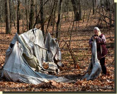 A traditional woodsman holds a piece of canvas removed from a wigwam.