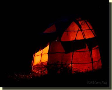 A small fire illuminates a wigwam at night.
