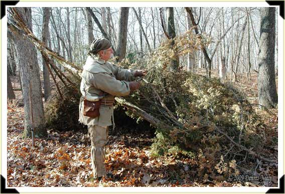 A traditional woodsman adds cedar boughs to a lean-to shelter.