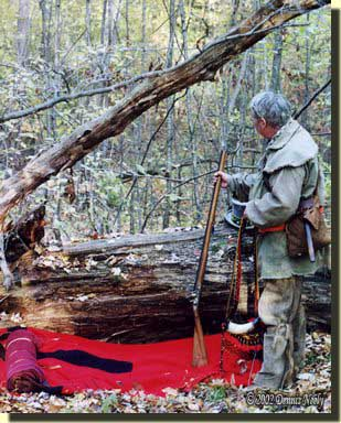 A tradtionial woodsman sets up a night camp beside a downed oak log.