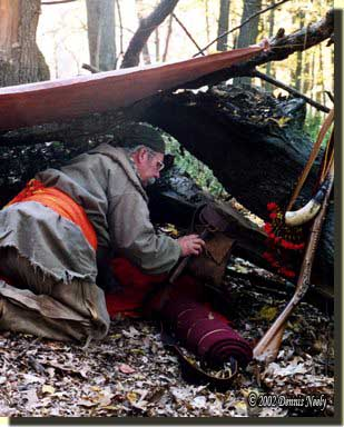 A traditonal woodsman adjusting gear in a night fall shelter.