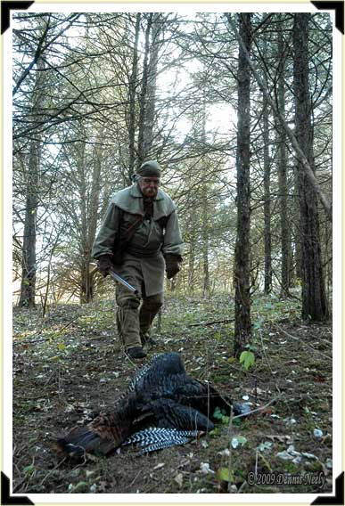 A trading post hunter approaches a downed wild turkey.