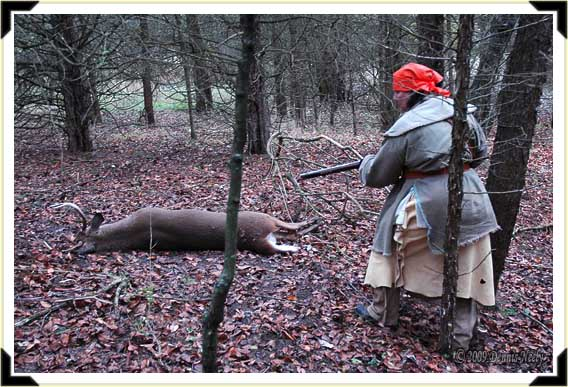 A Lady of the Woods approaches a downed buck with her trade gun shouldered.