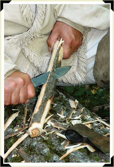 A butcher knife slices away cherry bark.