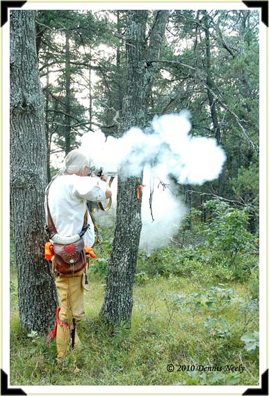 Smoke drifts as a woodsman fires at the 'mark.'