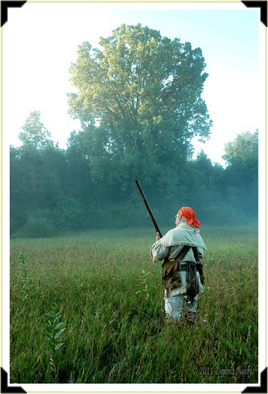 A traditional woodsman crosses a grassy prairie shrouded in a morning fog.