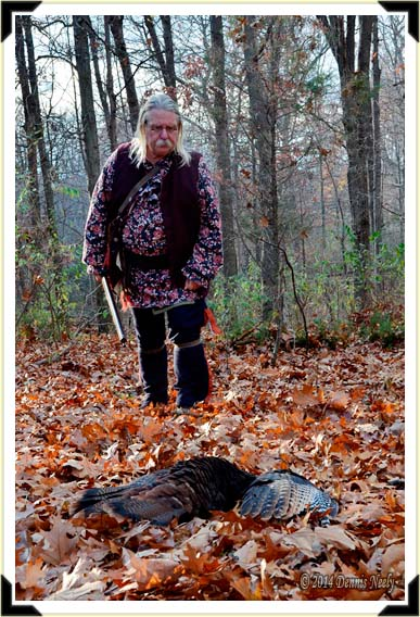 A traditional black powder hunter approaches a downed wild turkey.