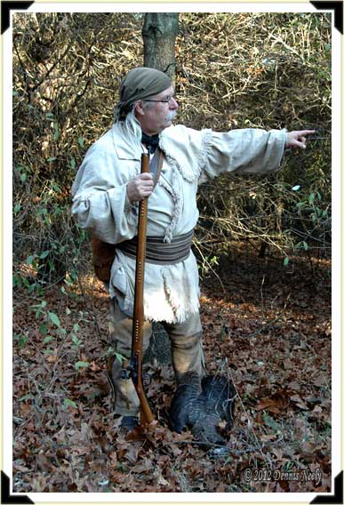 A traditional woodsman with a turkey at his feet.