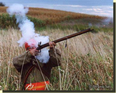 A traditional woodsman firing a flintlock at a fowl.