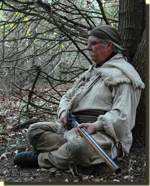 A traditional woodsman sits cross-legged watching the forest floor...