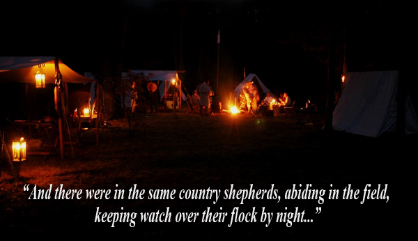 Woodsmen gather around a campfire in the dark of night.