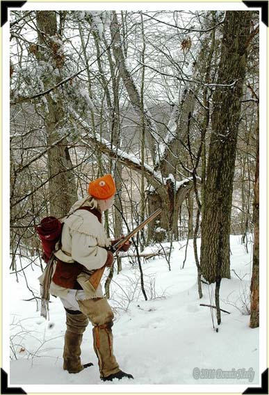 A traditional woodsman eases to a ridge crest in a snowy forest.