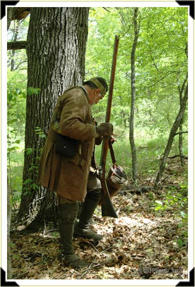 A British Ranger removes his bedroll and places it next to a large oak.