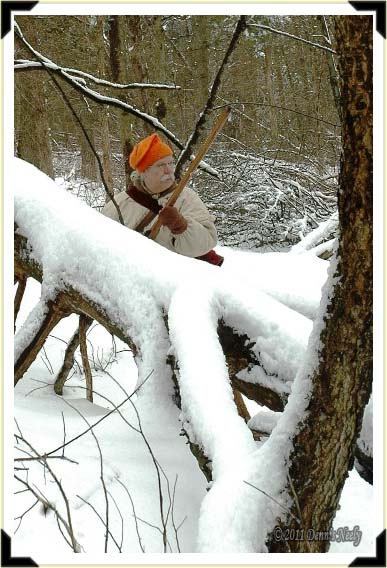 A traditional woodsman stands behind a snow-covered log.
