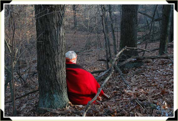 A traditional hunter, wrapped in a red trade blanket, sits against a tree.