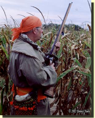 A traditional black powder hunter walks beside a corn field
