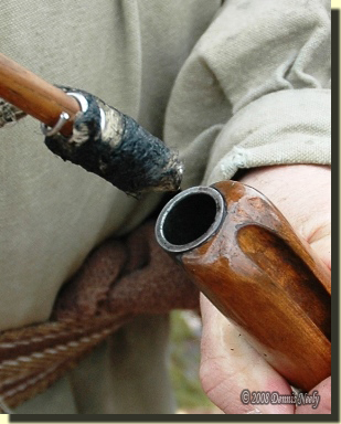 A tow swab covered with black powder fouling.
