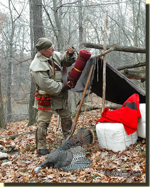A traditional woodsman returns to his lean-to shelter with a wild turkey.