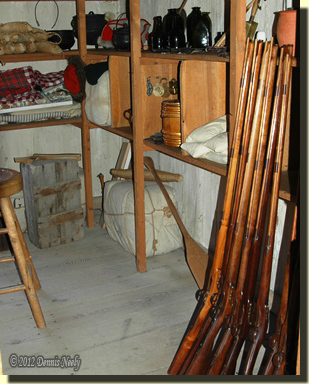 Northwest guns leaning against shelves of trade goods at Michilimackinac