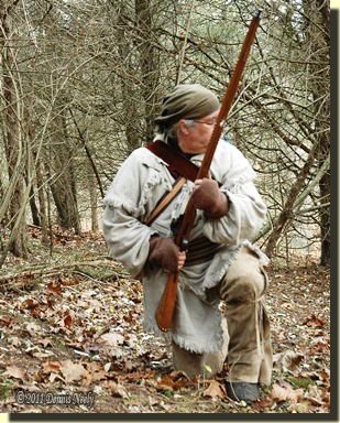 A traditional woodsman, kneeling in the midst of a wild turkey stalk.