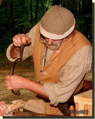 A frontier gunsmith bores a tang-bolt hole in a rifle stock with a crude brace and bit.