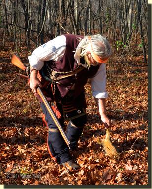 Msko-waagosh picks up a downed fox squirrel.