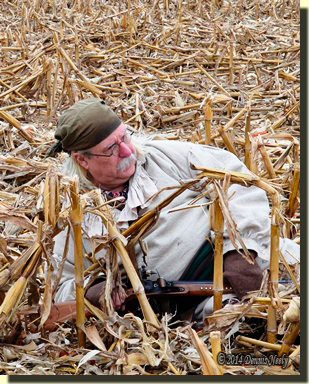 The traditional woodsman reclines in the stubble, half-covered with corn fodder.